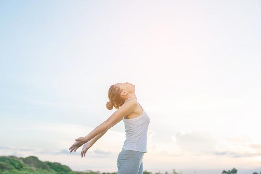Chica en libertad con un estilo de vida saludable mirando al cielo