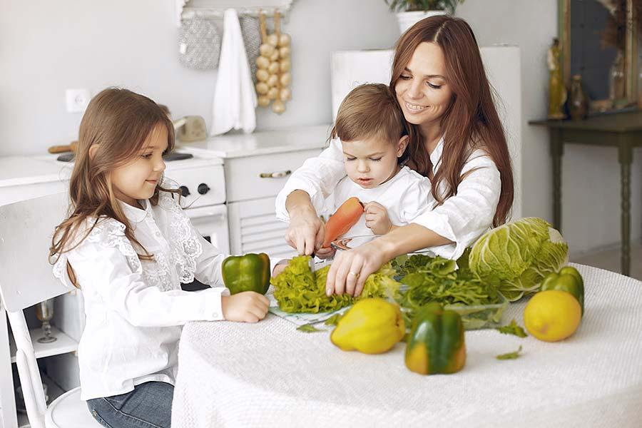 Madre con niños cortando verduras en la cocina