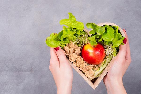 Cesta de madera con forma de corazón y hortalizas