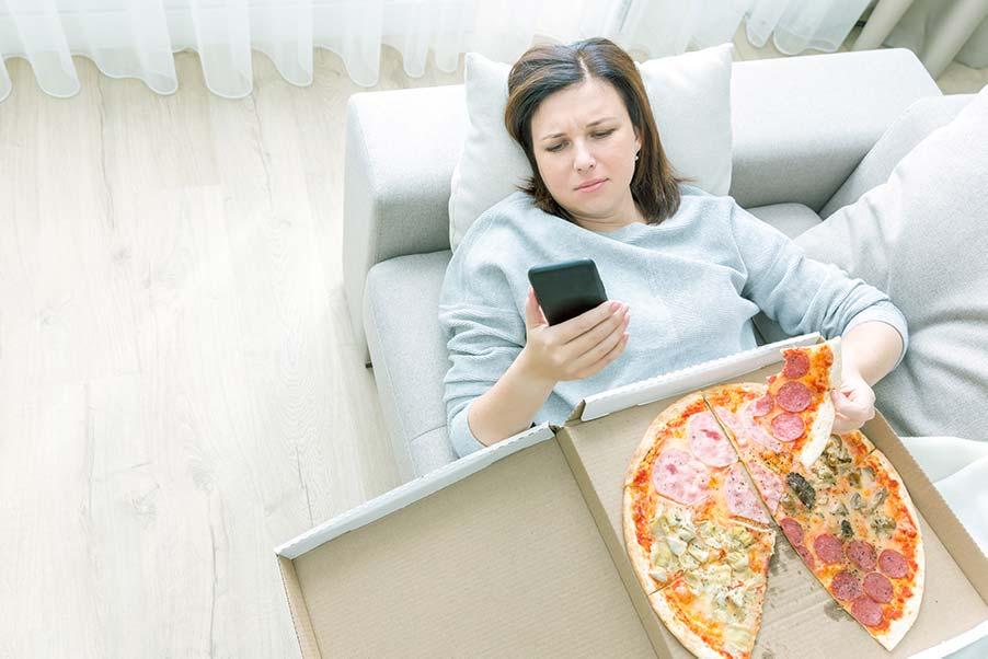 Mujer con estrés tumbada en sofá con móvil y comiendo pizza