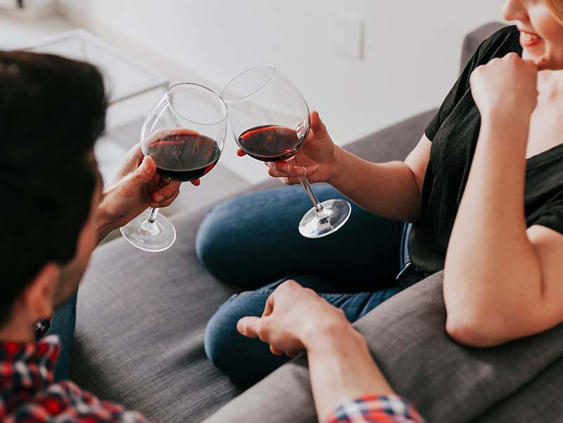 Pareja tomando vino tinto en el sofá y brindando