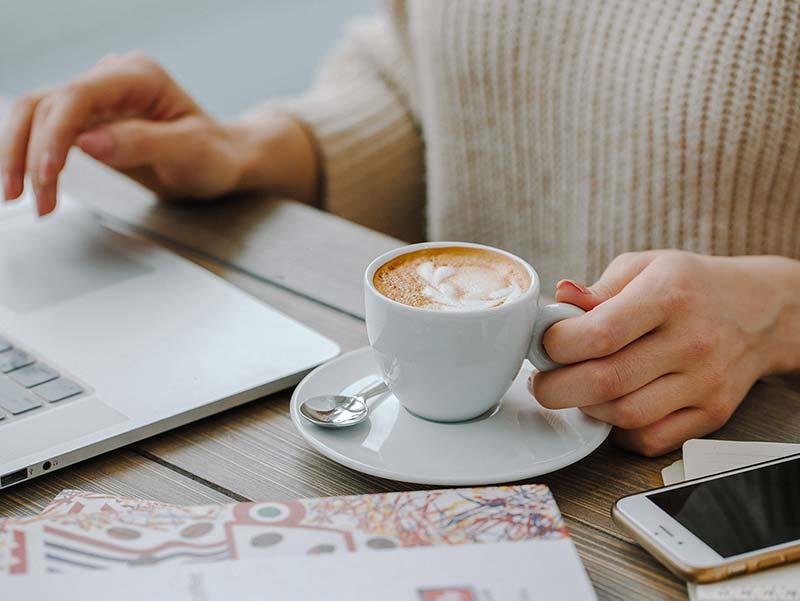Chica con taza de café trabajando en el ordenador