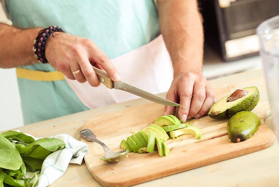Hombre cortando aguacates en la cocina para preparar una ensalada.