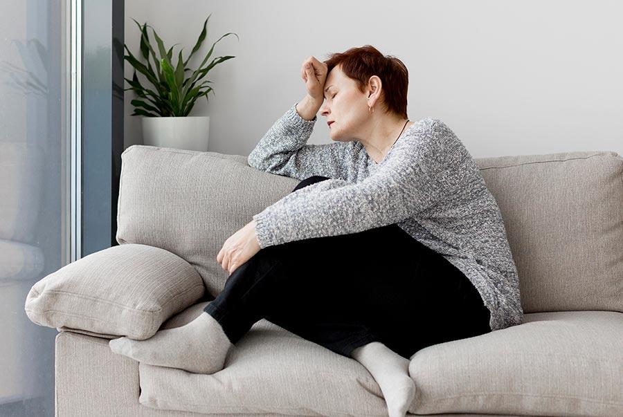 Mujer sentada en sofá pensativa y con estrés.