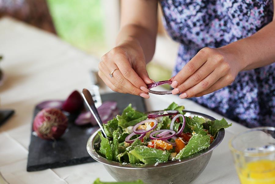 Mujer preparando una ensalada de verduras.
